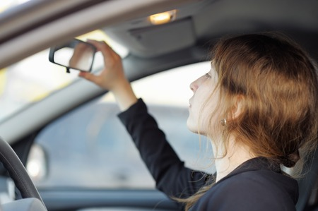 Young woman looking in the mirror in a car close up photo
