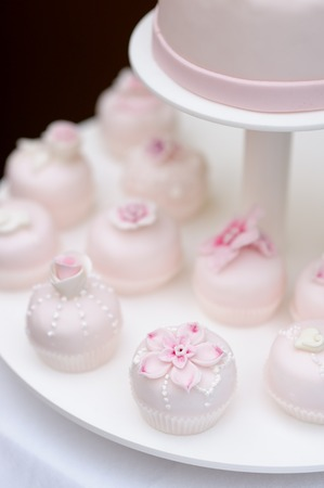 Delicious pink wedding cupcakes and cakes decorated with flowers photo