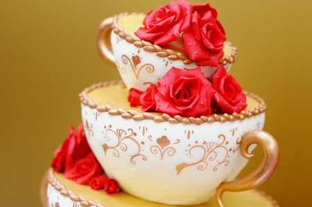 Delicious original wedding cake decorated with red flowers photo