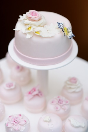 Delicious pink wedding cake and cupcakes decorated with flowers and butterfly photo
