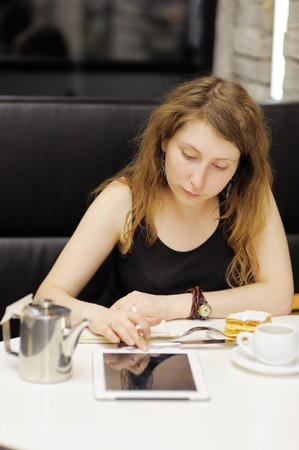 Young woman working or studing on her tablet computer in a cafe photo