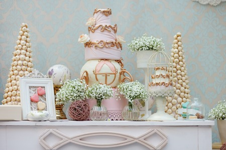Elegant sweet table with big cake and macaroon on dinner or event party  photo
