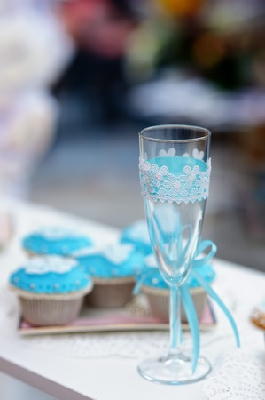 Stylish champagne glass and blue cupcakes photo