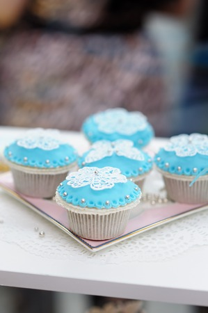 Stylish blue and white cupcakes on plate photo