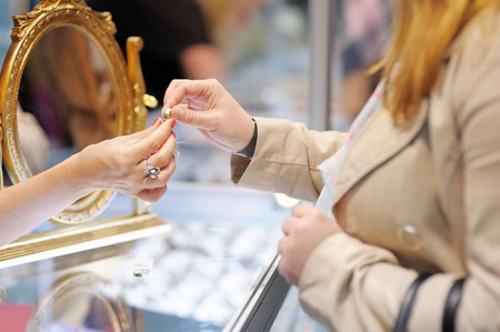 Woman trying wedding rings at a jeweler, focus on ring