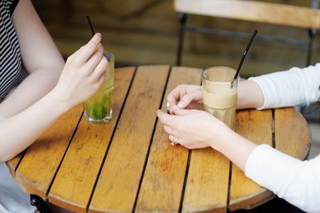 Hands with drinks of two girls Foto de archivo