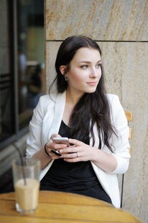 Young woman drinking ice coffee and using her mobile phone in a outdoor cafe photo