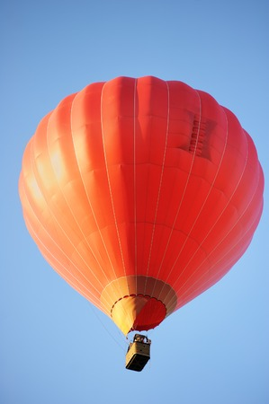 Red hot air balloon on blue background photo