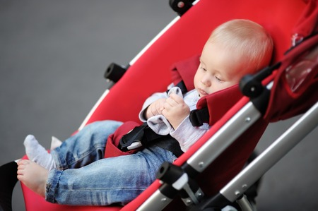 baby carriage: Little baby boy in stroller playing with his sock
