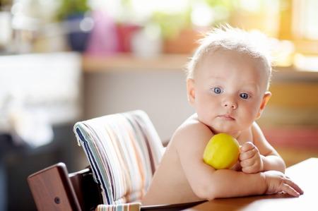 Cute baby boy eating healthy food (apple) photo
