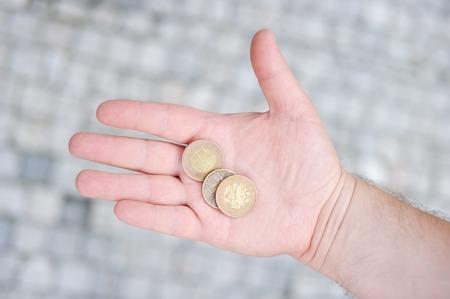 koruna: Man holding golden and silvery coins (czech koruna) in his hand