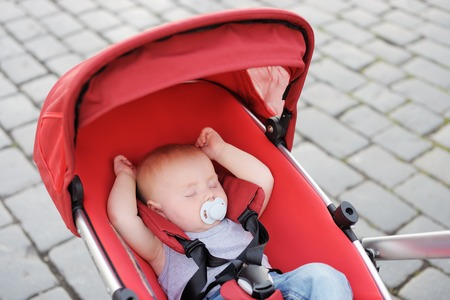 soother: Sweet little baby boy sleeping in stroller Stock Photo