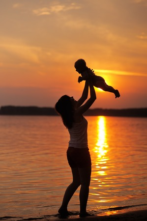 Portrait of young woman with little baby as silhouette by the water photo