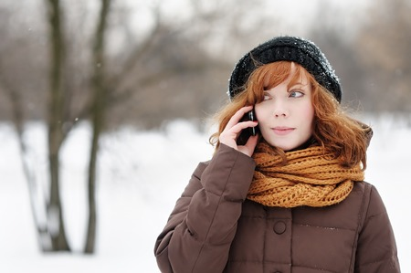 Outdoors portrait of young beautiful woman with mobile in winter