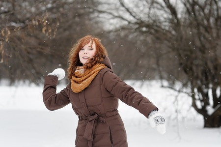 hurl: Young beautiful red haired woman having fun in winter