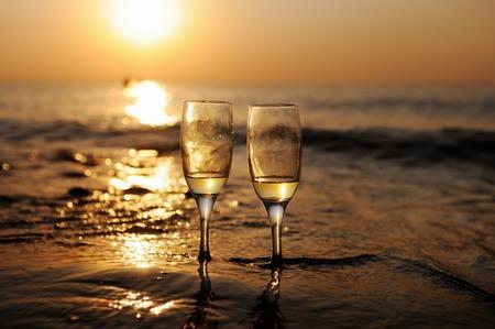 vacaciones playa: Noche rom�ntica de la playa en la puesta de sol con dos vasos de vino blanco Foto de archivo