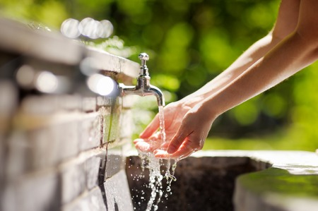 Closeup photo of woman washing hands in a city fountain Archivio Fotografico