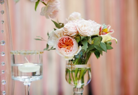 Flowers bouquet and candle as decoration on wedding party photo