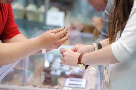 jeweller: Woman trying wedding rings at a jeweler, focus on ring
