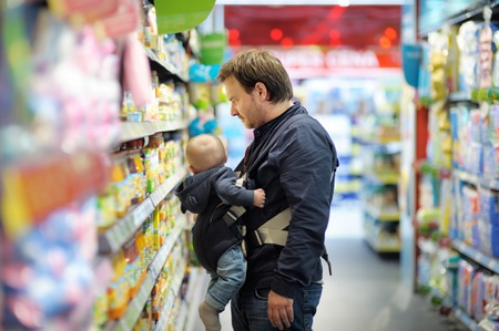 Father and his son on shopping at supermarket photo