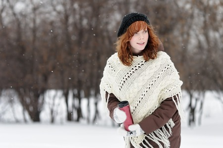 Young beautiful woman with metallic tumbler walking in winter park photo