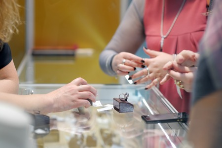 jeweler: Woman trying rings at a jeweler Stock Photo