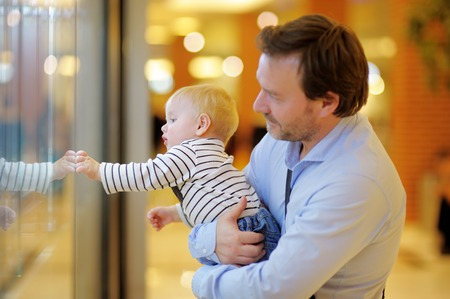 father and son holding hands: Father and his son at the shopping mall Stock Photo