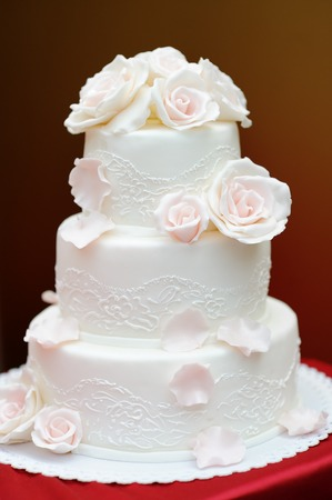 Delicious white wedding cake decorated with pink cream roses