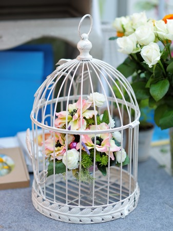 wedding ceremony: White cage with flowers as decoration on wedding