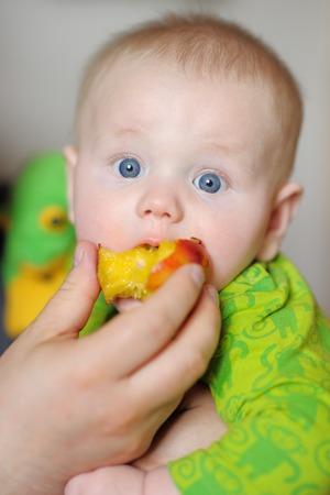 Cute baby boy eating healthy food (peach) photo