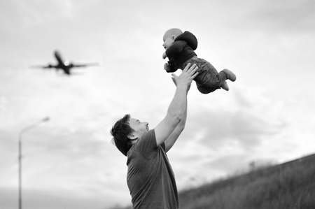 day dream: Father holding his baby (airplane on background)