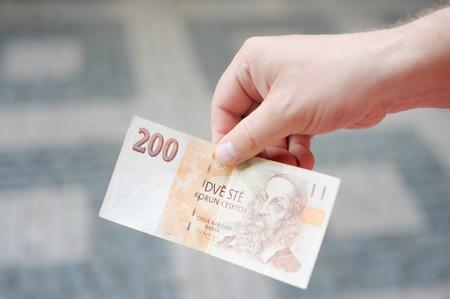 koruna: Man holding paper money (czech koruna) in his hand