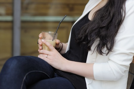 Young woman holding glass with ice coffee photo