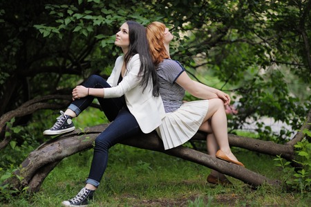 spat: Two beautiful young woman sitting on the tree