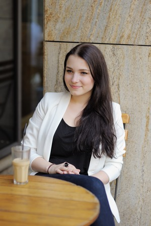 Young woman drinking ice coffee and in a outdoor cafe photo