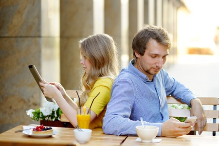 faithlessness: Young couple using smart phone and tablet pc in the outdoor cafe Stock Photo