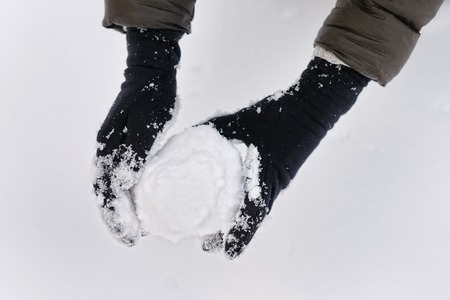 Woman holding snowball in her hands photo