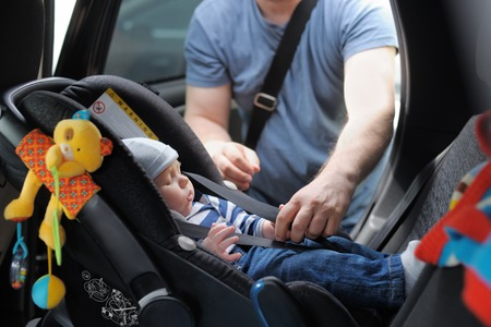baby on chair: Father fasten his little son in car seat Stock Photo