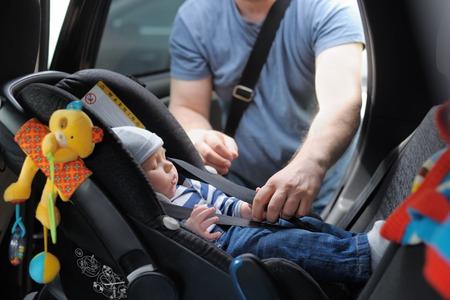 asiento coche: Padre fije su pequeño hijo en el asiento del coche Foto de archivo