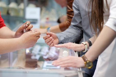 silver jewellery: Woman trying wedding rings at a jeweler, focus on ring