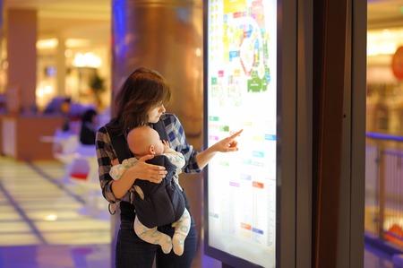 centro comercial: Mujer joven con su peque�o beb� en un centro comercial