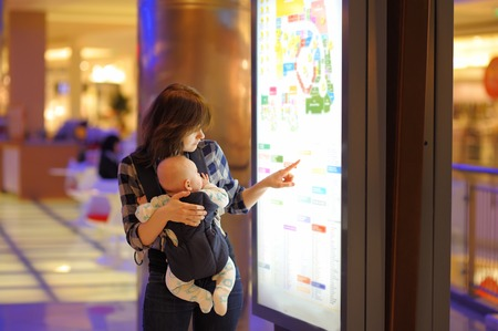 convenient store: Young woman with her little baby in a shopping mall