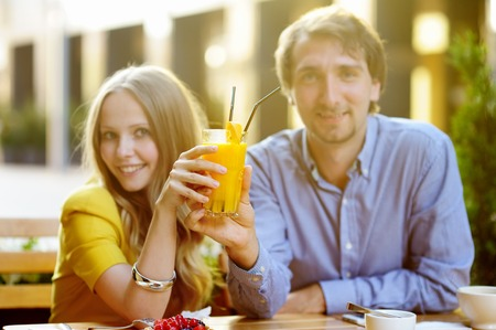 Young loving couple holding glass of orange juice (focus on glass) photo