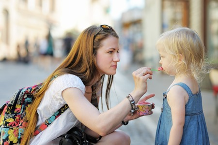 street child: Young mother and her daughter eating ice cream outdoors