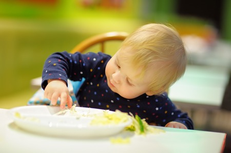 Toddler boy playing with food at the indoors cafe