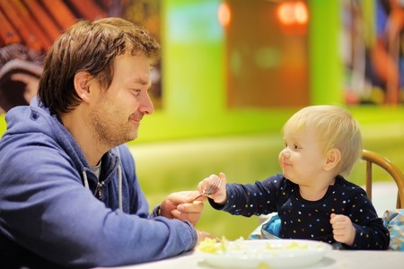 Toddler boy and his middle age father at the indoors cafe photo