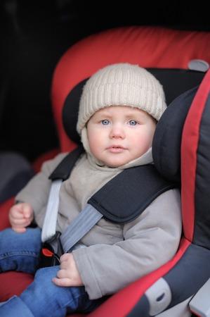 Portrait of toddler boy sitting in car seat photo