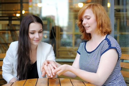 Portrait of two young woman at the outdoors cafe photo