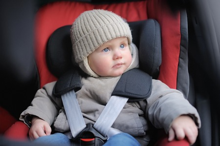 Portrait of toddler boy sitting in car seat Stockfoto