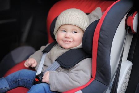 Smiling toddler boy sitting in car seat photo